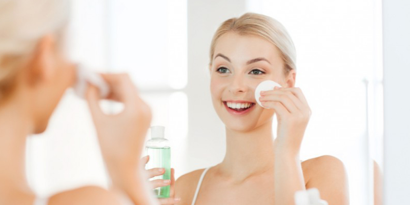 A Smiling Woman Appliying Cream On Her Face Infront Of The Mirror.