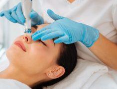 A Beautician Applies Facial Cream On A Young Woman Face.