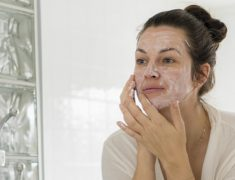 A Woman Applies Facial Cream On Her Face.