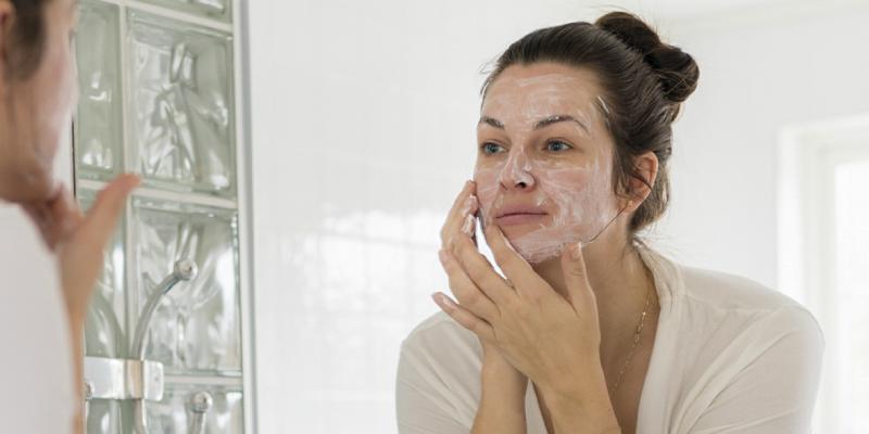 A Woman Applies Facial Cream On Her Face.